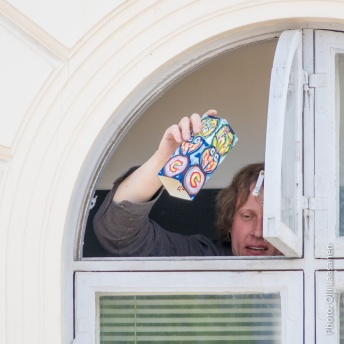 Erki starts to drop painted cartons from his residence' window.